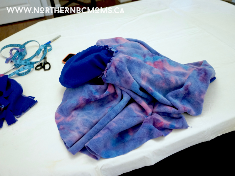 DIY No Sew Fleece Poncho for Toddlers - Pull the neck through the circle to put the knots on the inside of the poncho